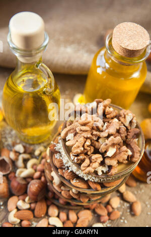 oil and nuts on a wooden background - Stock Photo