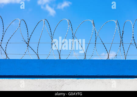 Barbed wire on the fence against a blue sky background - Stock Photo