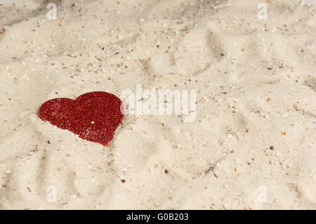 Red heart lying in the sand - Stock Photo