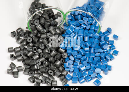blue and black polymer pellets in test tubes - Stock Photo
