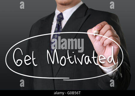 Motivational business concept, image of a businessman holding marker and write Get Motivated words - Stock Photo