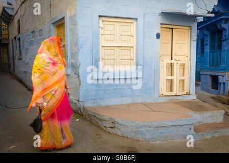 Woman in colourful sari walking past blue house in Jodhpur - Stock Photo
