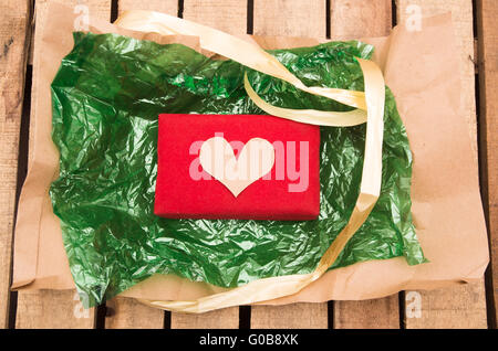 Red present lying on green plastic with golden ribbon string around it, as seen from above - Stock Photo