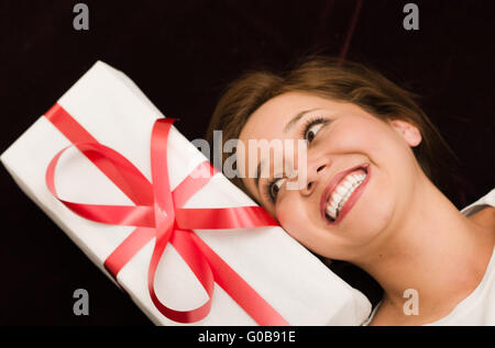 Closeup brunette headshot as seen from above, big smile and resting head next to present with white wrapping paper - Stock Photo