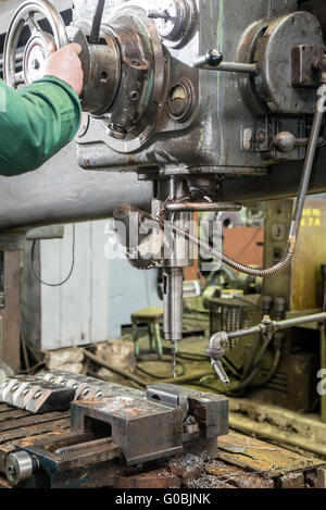 machinist working on industrial drilling machine in workshop - Stock Photo