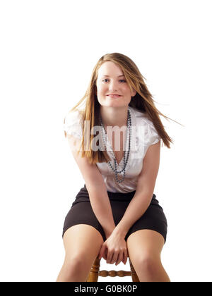 Young woman in white blouse and black skirt sitting - Stock Photo