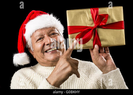 Avid Aged Man Pointing At Golden Wrapped Present - Stock Photo