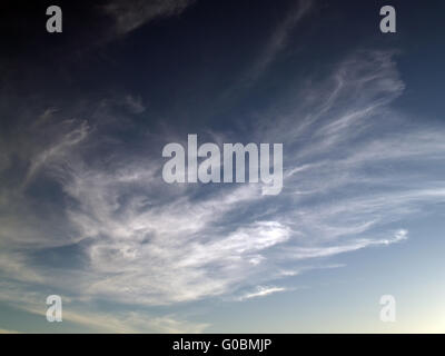 High clouds in sky going from light to dark - Stock Photo