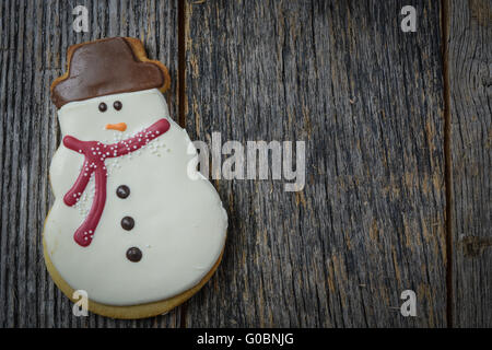 Snowman Cookie on Rustic Wood Background for Christmas - Stock Photo