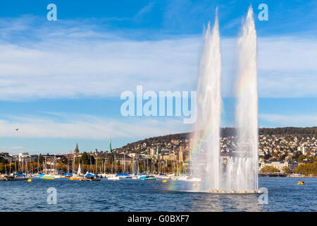 Beautiful view of the fountain at  Mythenquai with rainbow in the Zurich lake and the cityscape of Zurich old town - Stock Photo