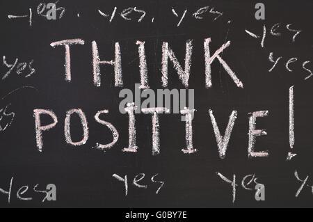 think positive concept handwritten on black chalkboard - Stock Photo