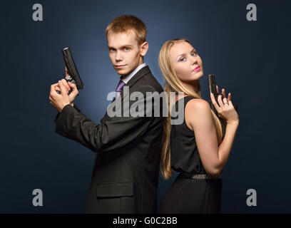 beautiful spy couple in evening dress with a guns. - Stock Photo