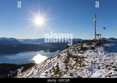 Summit cross of Mt. Jochberg with Walchen Lake - Stock Photo