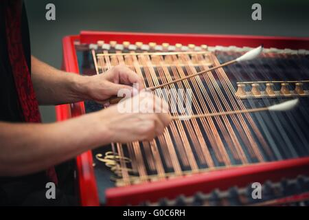 Playing the dulcimer folk musical instrument from Europe - Stock Photo
