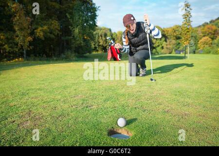 Female - golf player on knees and arms raised with putter in hand in winner pose on golf green being overjoyed as - Stock Photo