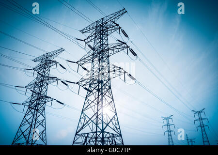 high voltage electricity transmission pylon silhouetted - Stock Photo