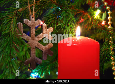 Christmas - candle and wooden snowflake on fir - Stock Photo