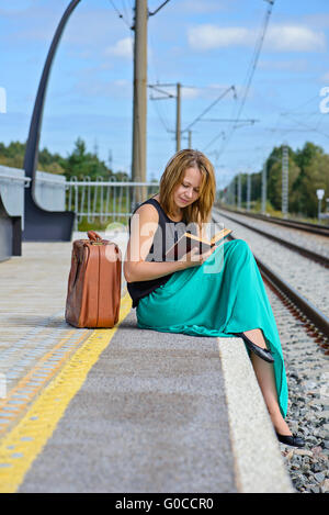 Young girl sitting on the station and reading - Stock Photo