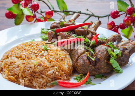 Close up view of grilled lamb chop served with rice, with spicy red chili, coriander, etc - Stock Photo