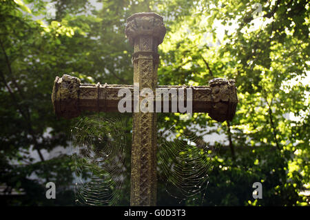 Old grave cross with cobwebs - Stock Photo