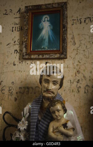 Statue of Joseph with baby Jesus in abandoned church at Bokor Hill Station, Cambodia. - Stock Photo