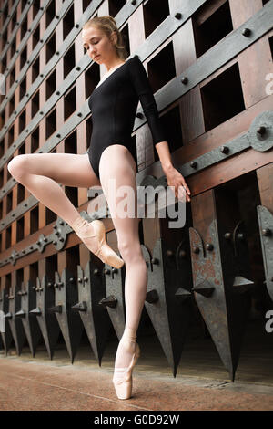 Slim dancer stands on one leg near the old gate - Stock Photo