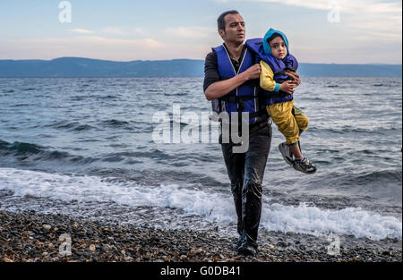 Syrian father and son come ashore on the Greek island of Lesvos after crossing from Turkey in a raft - Stock Photo
