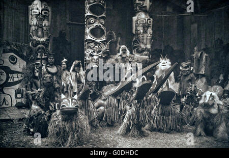 Native American Kwakiutl or Qagyuhi dancers wearing masks and costumes during a traditional potlatch 1914 in British - Stock Photo