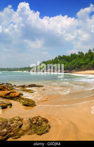 sea waves on tropical beach with stones and rocks