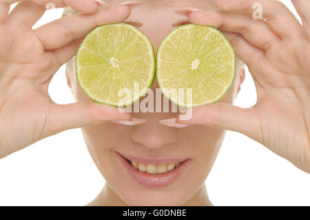 Young woman holds halves of lime before eyes - Stock Photo