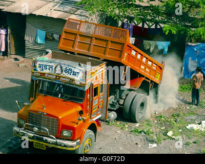 Downloading debris from a lorry/dumper is going on near a construction site - Stock Photo