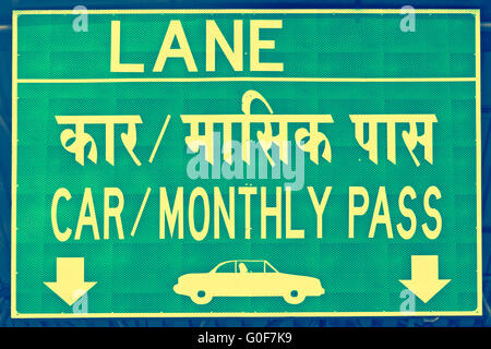 A Notice board showing a lane for car with monthly pass vehicles at a toll Pune - Stock Photo