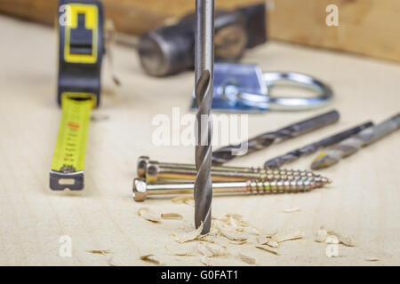 Drill drilling into the wood with sawdust and tool - Stock Photo