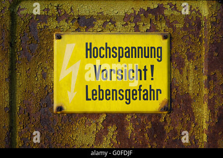 yellow warning sign that says high voltage Caution mortal danger - Stock Photo