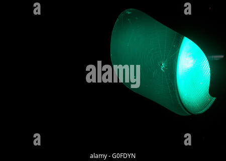 Spider in it spiderweb attached to a green traffic light. - Stock Photo