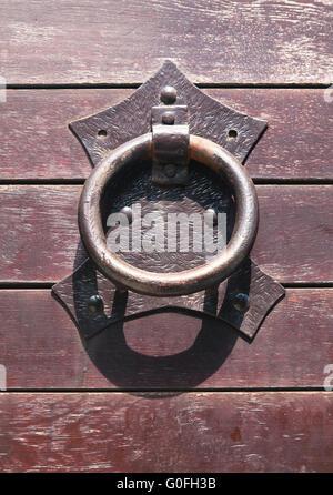 Metal ring door knocker on a medieval wooden door - Stock Photo