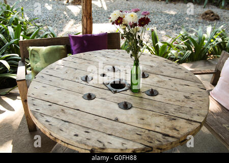Wooden table in restaurant made from recycled material - Stock Photo