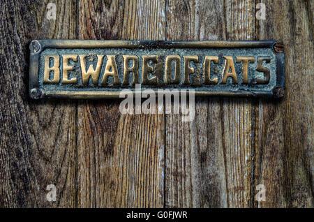Beware Of Cats Sign On Wooden Door - Stock Photo