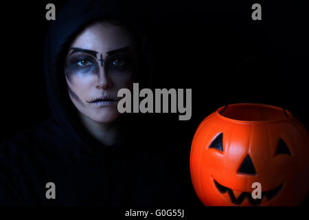 Girl dressed in scary face paint with pumpkin bucket on black background - Stock Photo