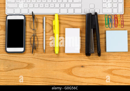 Office work supplies align with computer keyboard on desktop - Stock Photo