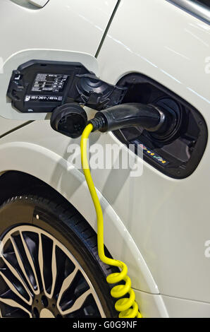 charging cable at the tail of a modern electric driven car - Stock Photo