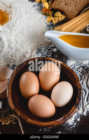 Pasta on dark wooden background with eggs, oil and flour close-up macro - Stock Photo