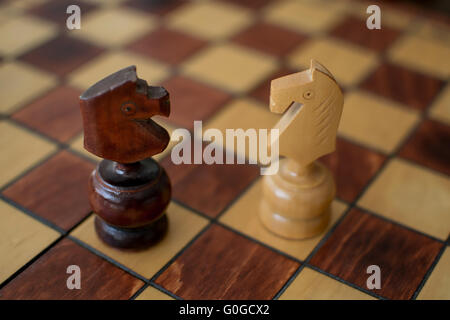 Two Knights on a wooden chessboard - Stock Photo