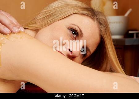 Young woman receiving an honey-salt-massage - Stock Photo