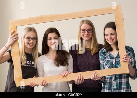 Girl group smiling through a nature photo frame - Stock Photo