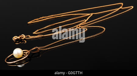 Golden chain with pendant on black mirrored surface - Stock Photo
