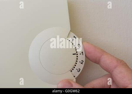 Setting the room thermostat and save on heating costs - Stock Photo