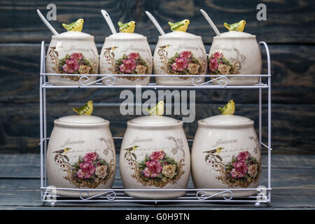 Ceramic round jars with flower ornaments and birds on blue wooden background - Stock Photo