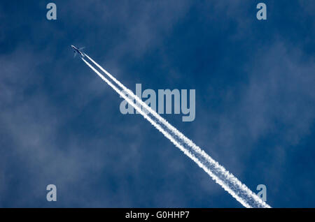 A passenger jet flying over the UK. - Stock Photo