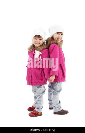 Identically dressed little girls posing in studio - Stock Photo